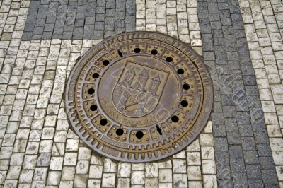 Sewer manhole with emblem of Prague