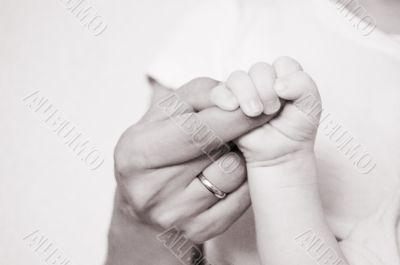 Baby holds mother finger