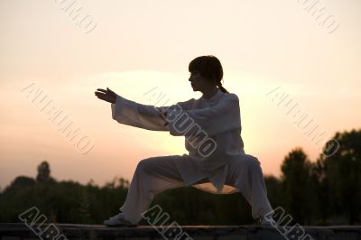 woman in white suit make`s taiji chuan exercise
