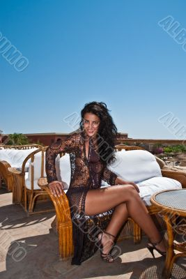 The glamour model poses on a terrace at midday