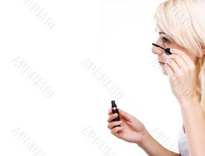 happy young woman using mascara