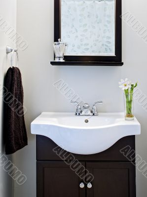 Black and white designer bathroom with mirror and flower