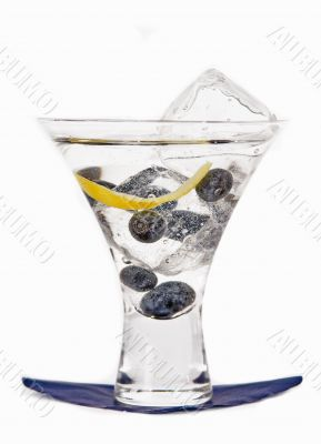 Blueberry cocktail in a glass with blueberries and ice cube on a