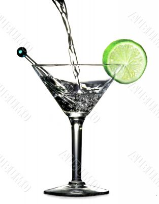 Pouring alcohol in a martini glass with slice of lime