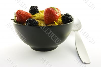 Cornflakes and Fruit in a Black Bowl with a Spoon