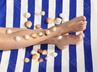 feet with shells on towel