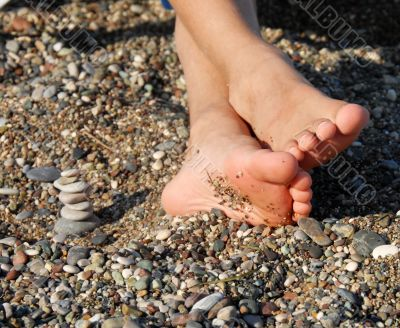 Rocks stack and boy feet
