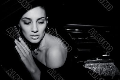 The glamour model poses in the black car