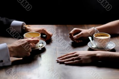 Bride`s and groom`s hands holding coffee cups