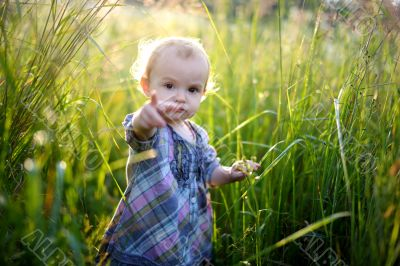 Little baby in an overgrown grass pointing at you