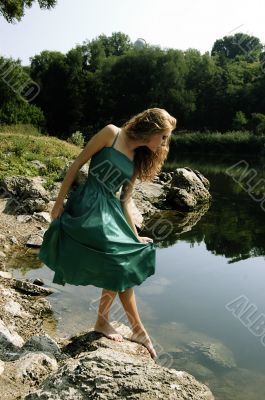 Sensual girl in dress near lake