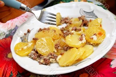 Baked potatoes with meat in plate