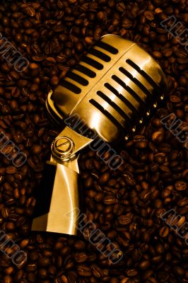 Retro-styled microphone laying on a coffee beans.