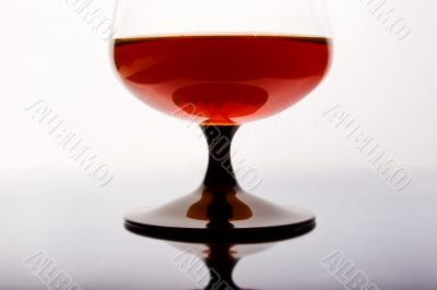 Glass of cognac standing on mirror table.