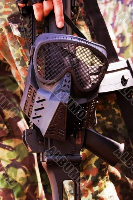 Black military mask hanging on a rifle