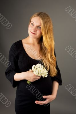 smiling gentle young pregnant blonde woman