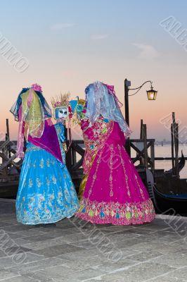 Venice Carnival masks looking at hand mirrors