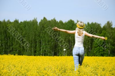 happy young woman is standing on a field