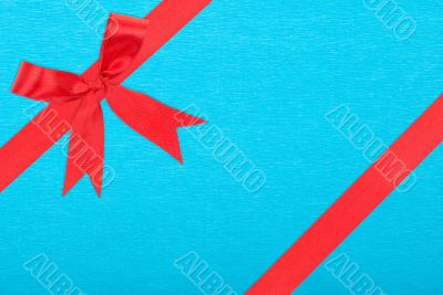 Red satin ribbon and bow gift box wrapping over blue paper backg