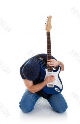 rocker playing guitar kneeling