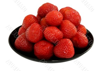 Ripe berries of a strawberry on black saucer