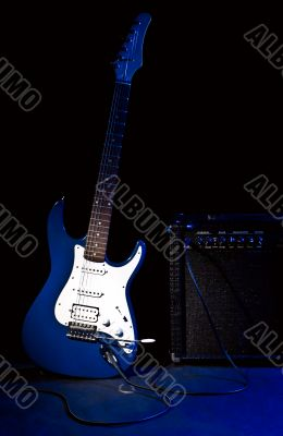 electric guitar and combo amplifier in rays of blue light