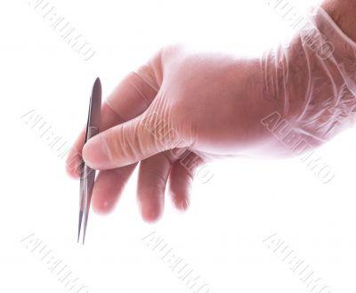 hand in rubber glove holding tweezers