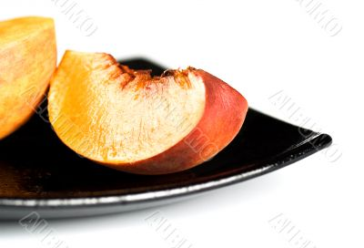 red peaches slices on black dish
