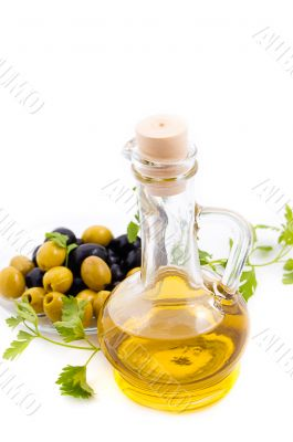 Olives and oil in jug with greens
