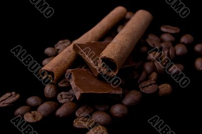 Cinnamon sticks over coffee beans and chocolate