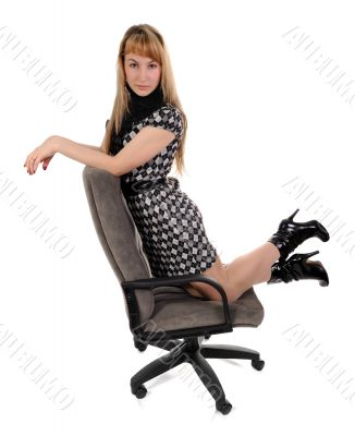 The girl kneeling in office armchair