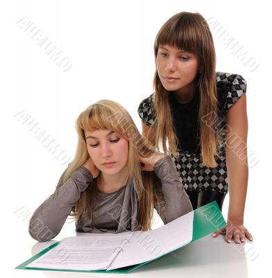 Two girls read documents.
