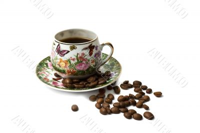 Coffee cup with scattering of coffee beans. Isolated on a white