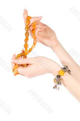 Hands holding amber necklace and bracelet