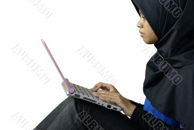Serious muslim asian lady using laptop