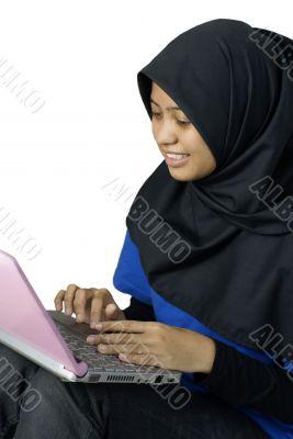 Happy asian muslim lady using laptop