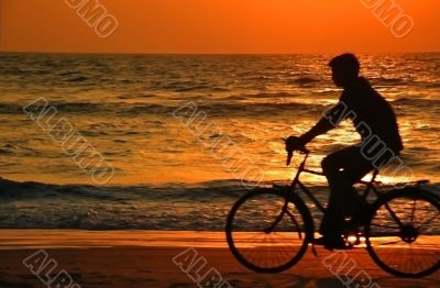 Cycling At Sunset On The Beach