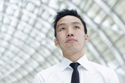 Asian male executive looking up