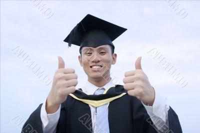 Happy asian graduate thumbs up