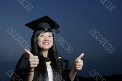 Smiling asian female graduate with thumbs up sign