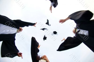 Happy graduates throw hats