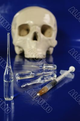 Medical syringe, ampoules and skull