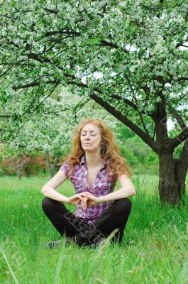 Woman meditating under blooming tree