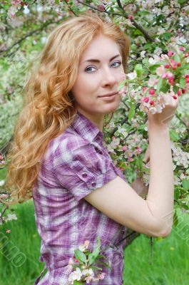 Red-haired woman among apple blossom
