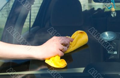 The hand washes a yellow rag the car
