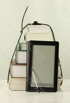 Stack of books and electronic book reader