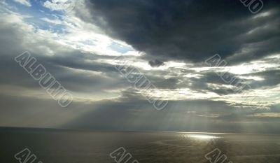 Sun ray flow through the clouds over sea