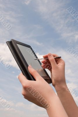 Hands hold electronic book reader against blue sky