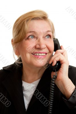 Senior Woman talking on the phone in black suite.