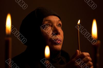 Senior Woman in black clothes with candle.